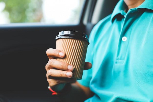 Ein mann mit dem grünen hemd, das einen tasse kaffee im auto hält. Premium Fotos