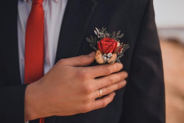 Ein mann mit einem ehering am finger hält einen hochzeitsboutonniere an seiner jacke. hände des brautpaares in nahaufnahme Premium Fotos