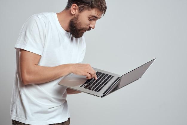 Ein mann mit einem laptop in seinen händen auf einem hellen raum in einem weißen t-shirt emotionen lichtraum beschnitten ansicht modell porträt neue technologien. Premium Fotos