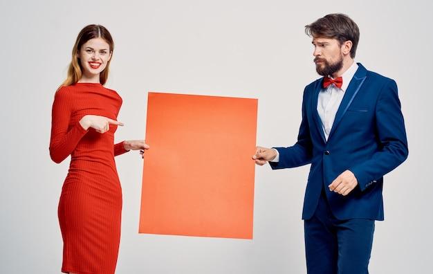 Ein mann mit einem roten blatt papier in den händen und einer frau in einem kleid mocap poster werbung Premium Fotos