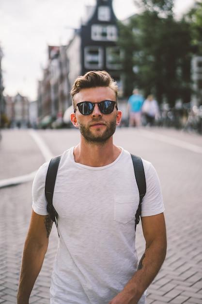 Ein mann mit einem rucksack geht durch die straßen von amsterdam. Kostenlose Fotos