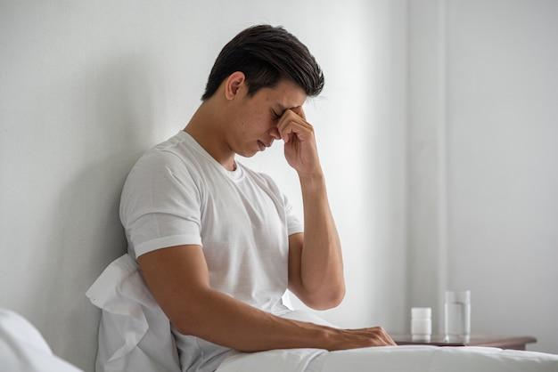 Ein mann mit migräne hält ihre hand an seiner nase im bett. Kostenlose Fotos