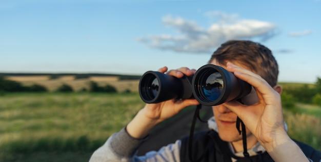 Ein mann mit modernen ferngläsern gegen den himmel und die grünen hügel. das konzept von jagd, reisen und erholung im freien. Premium Fotos