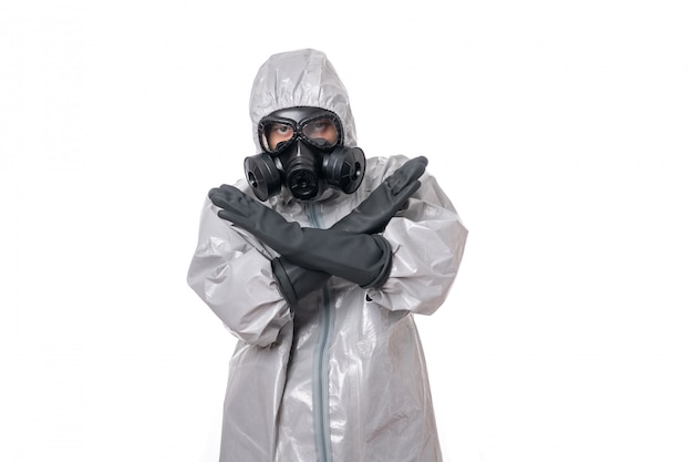 Ein mann posiert in einem grauen schutzanzug mit einem gelben strahlenschutzschild und einer schutzgasmaske Premium Fotos