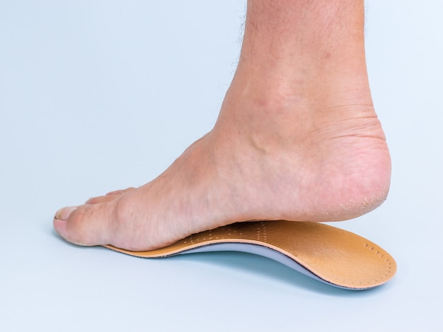 Ein mann probiert das rechte bein mit anzeichen einer orthopädischen einlegesohle für plattfüße an. mittel zur behandlung von plattfüßen. Premium Fotos