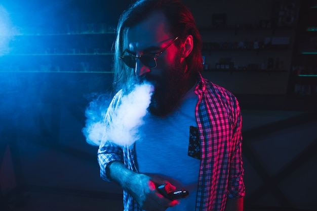 Ein mann raucht eine zigarette und lässt in einem nachtclub rauchen. Premium Fotos