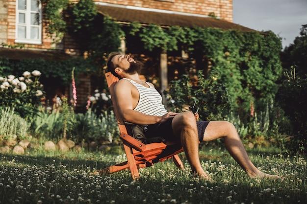Ein mann ruht sich in einem landhaus aus. ein bärtiger mann genießt den sonnenuntergang auf einem grünen rasen. Kostenlose Fotos