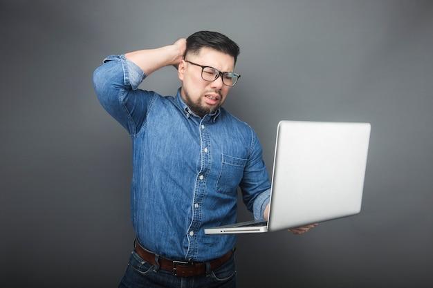 Ein mann sah überrascht auf den computer. Premium Fotos
