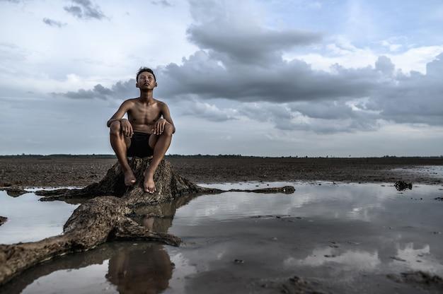 Ein mann saß mit gebeugten knien da und schaute zum himmel am fuße des baumes, umgeben von wasser. Kostenlose Fotos