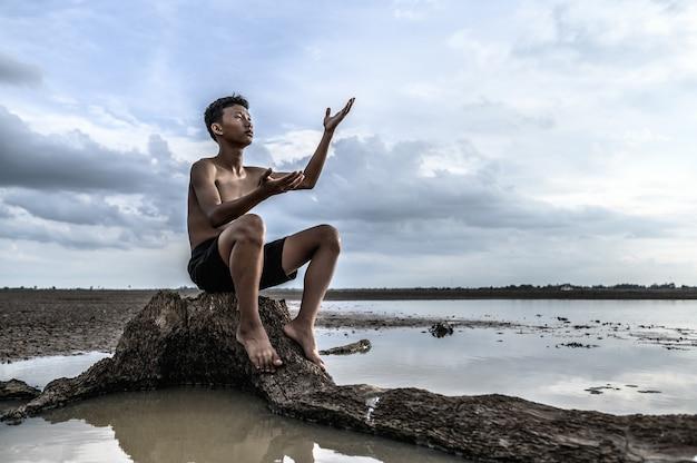 Ein mann saß mit gebeugten knien, machte ein handsymbol, um am baumstamm nach regen zu fragen, und war von wasser umgeben. Kostenlose Fotos