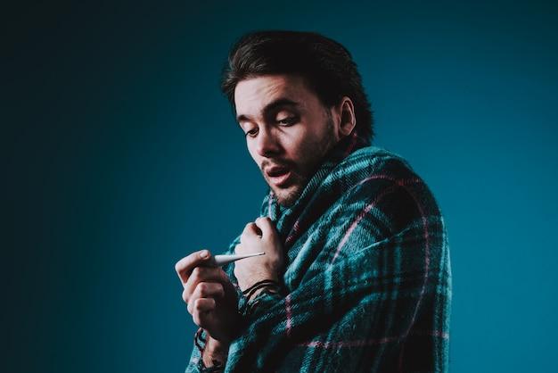 Ein mann schaut überrascht auf das thermometer. Premium Fotos