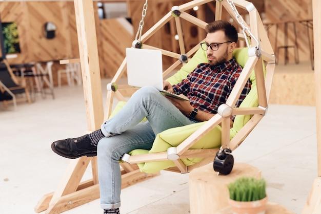 Ein mann sitzt auf einem hängenden stuhl. Premium Fotos