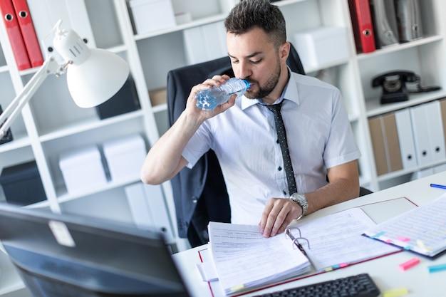Ein mann sitzt im büro an einem tisch, arbeitet mit dokumenten und trinkt wasser aus einer flasche. Premium Fotos