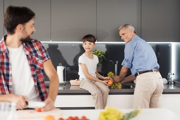 Ein mann steht in der küche und schneidet gemüse Premium Fotos