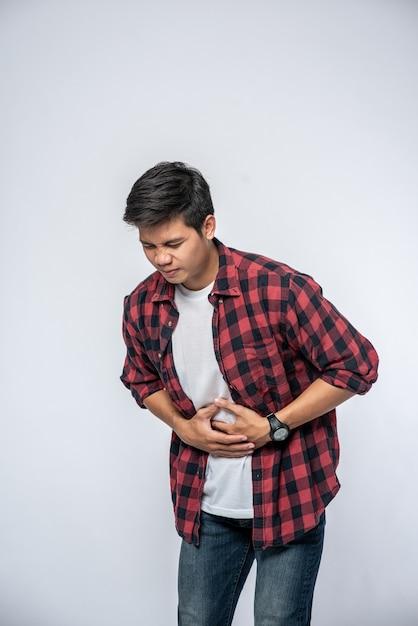 Ein mann steht mit bauchschmerzen und legt seine hand auf den bauch. Kostenlose Fotos