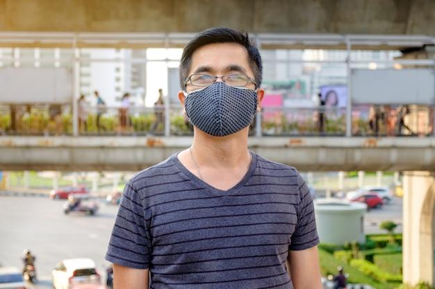 Ein mann trägt eine brille und eine schwarze mundmaske gegen luftverschmutzung mit pm 2.5 in bangkok thailand Premium Fotos