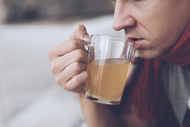 Ein mann trinkt orange heiltee aus einem glaskrug Premium Fotos