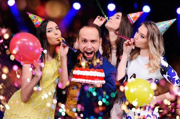 Ein mann und drei mädchen freuen sich und feiern die party im nachtclub Premium Fotos