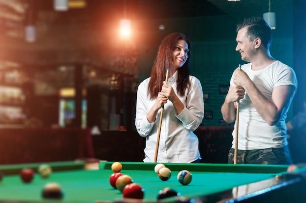 Ein mann und ein schönes mädchen spielen billard, ein mann bringt einem mädchen das billardspielen bei Premium Fotos
