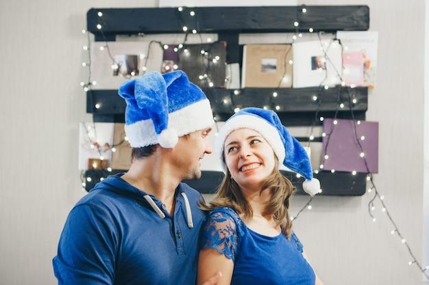 Ein mann und eine frau in der weihnachtsblauen hutumarmung. Premium Fotos