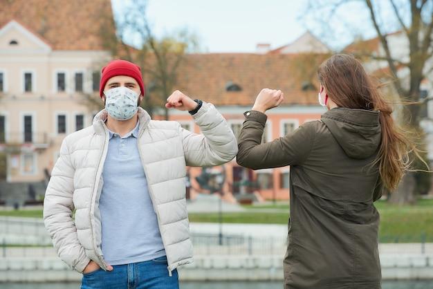 Ein mann und eine frau in gesichtsmasken stoßen an die ellbogen, anstatt sie mit einer umarmung zu begrüßen Premium Fotos