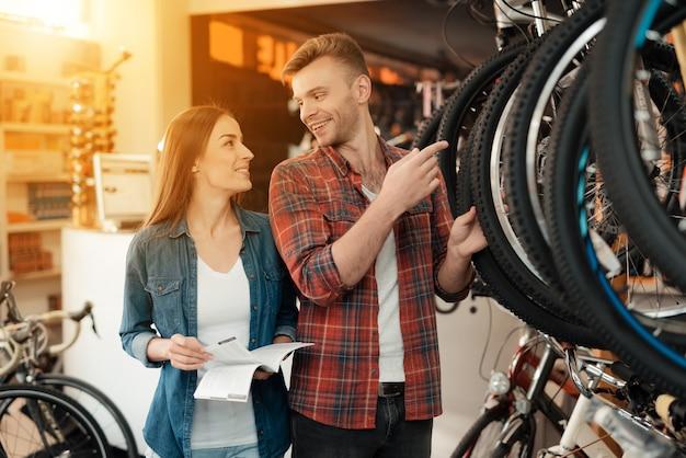 Ein mann und eine frau schauen sich aufmerksam verschiedene fahrräder an Premium Fotos