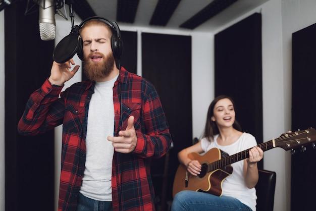 Ein mann und eine frau singen ein lied in einem tonstudio. Premium Fotos