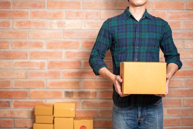 Ein mann unternehmer inhaber kmu-geschäft ist verpackung box, um seinen kunden zu senden Premium Fotos