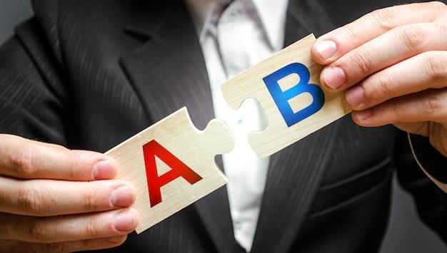 Ein mann verbindet rätsel mit den buchstaben a und b. a / b testet marktforschungsmethode Premium Fotos