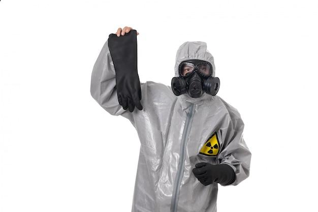 Ein mann wirft in einem grauen anzug, mit einer gasmaske auf und wirft auf dem weißen hintergrund auf Premium Fotos