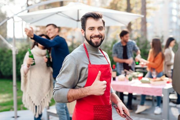 Ein mann zeigt daumen beim kochen von gemüse auf dem grill. Premium Fotos