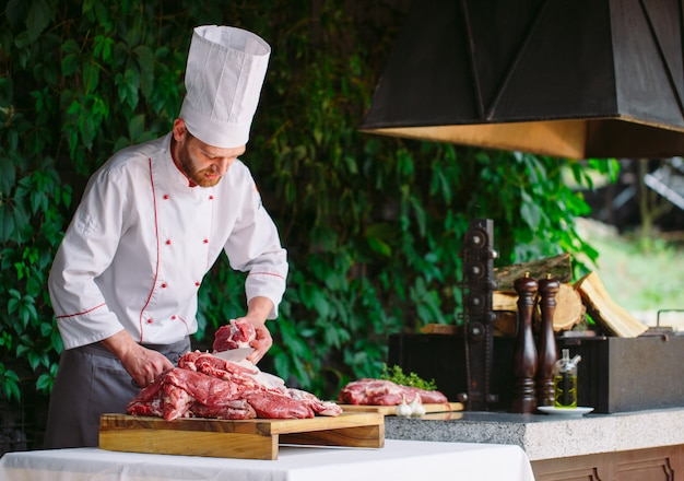 Ein mannkoch schneidet fleisch mit einem messer in einem restaurant. Premium Fotos