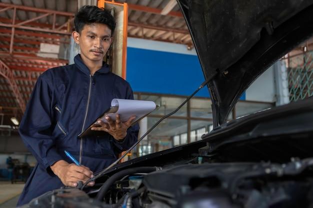 Ein mechaniker-service-auto in der garage ist papiercheck eine liste autos. Premium Fotos