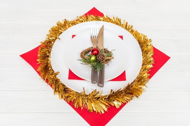 Ein messer und eine gabel in der weißen platte auf der roten serviette verziert mit einem weihnachtskranz auf weißer tabelle Premium Fotos