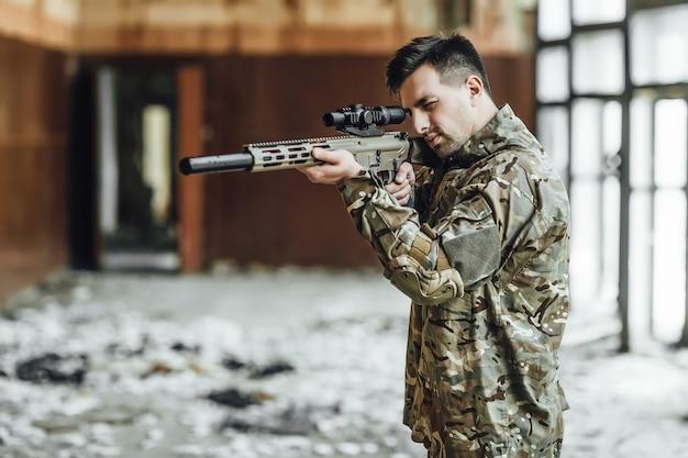 Ein militärsoldat zielt und hält ein großes gewehr im gebäude Premium Fotos