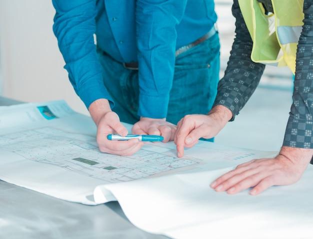Ein mitarbeiter zeigt einem anderen wichtige details im architekturplan eines projekts. Kostenlose Fotos