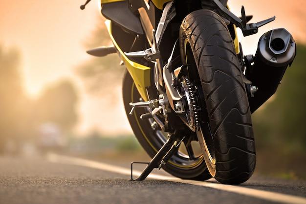 Ein motorradparken auf der rechten straßenseite und sonnenuntergang Premium Fotos