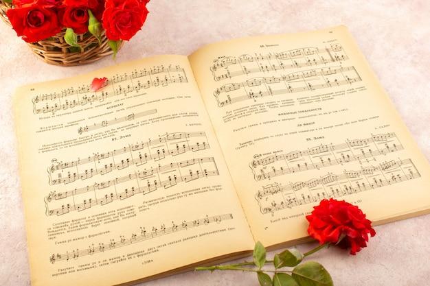 Ein musiknotenbuch von oben mit geöffneten roten rosen auf rosa Kostenlose Fotos