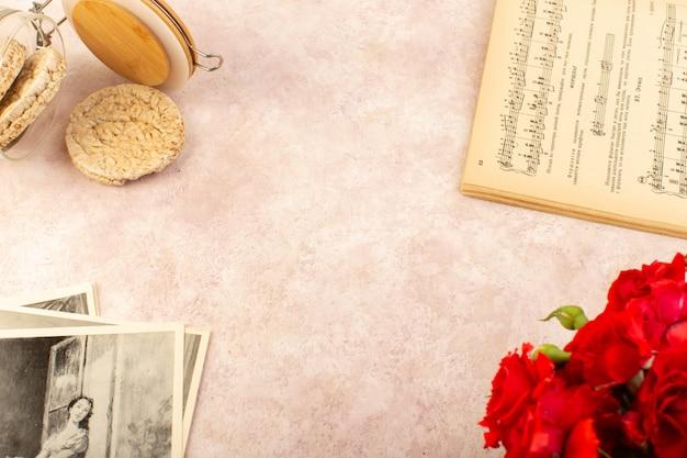 Ein musiknotenbuch von oben mit geöffneten roten rosenchips und fotos auf pink Kostenlose Fotos