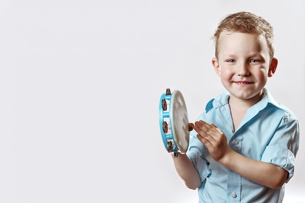 Ein netter junge in einem blauen hemd, das ein tamburin hält und auf einem hellen hintergrund lächelt Premium Fotos