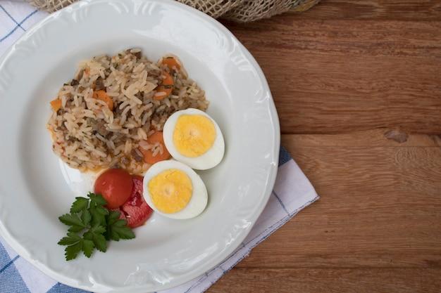 Ein netter teller des reises, der gekochten eier und der tomaten in der draufsicht Premium Fotos