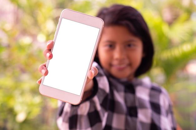 Ein nettes kleines asiatisches mädchen, das smartphone mit weißem leerem bildschirm zeigt Premium Fotos