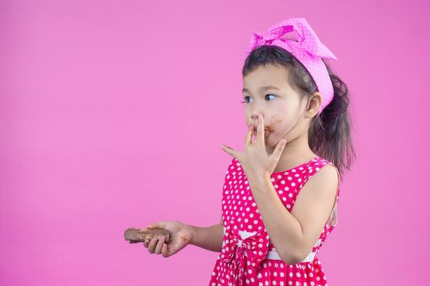 Ein nettes mädchen, das ein rotes gestreiftes hemd isst eine schokolade mit einem schmutzigen mund auf dem rosa trägt. Kostenlose Fotos
