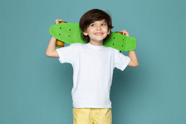 Ein niedlicher junge der vorderansicht im weißen t-shirt und in den gelben jeans, die grünes skateboard auf dem blauen raum halten Kostenlose Fotos