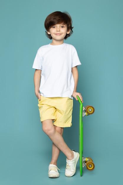 Ein niedlicher kinderjunge der vorderansicht im weißen t-shirt und in den gelben jeans, die grünes skateboard auf dem blauen boden halten Kostenlose Fotos