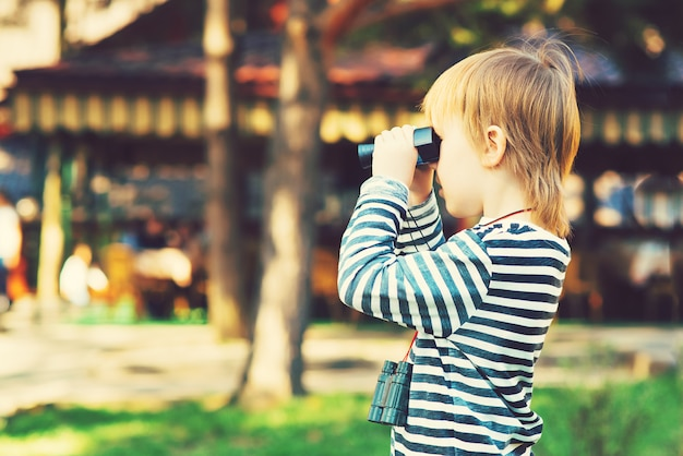 Ein niedlicher kleiner junge, der durch das fernglas im freien schaut. Premium Fotos