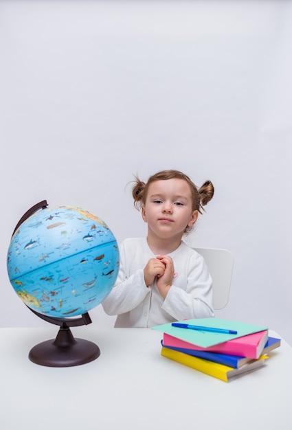 Ein niedlicher student sitzt an einem tisch mit lehrbüchern und einem globus Premium Fotos