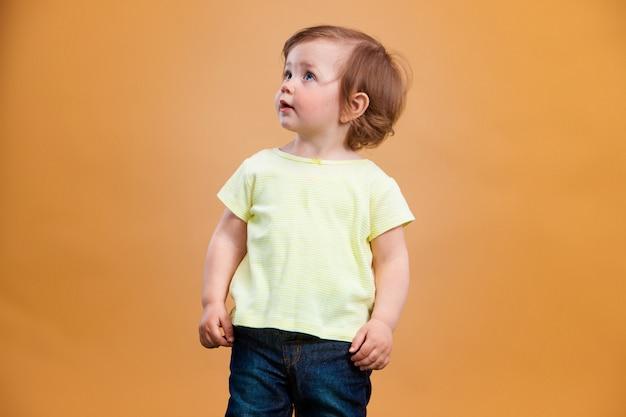 Ein niedliches baby auf orange hintergrund Kostenlose Fotos