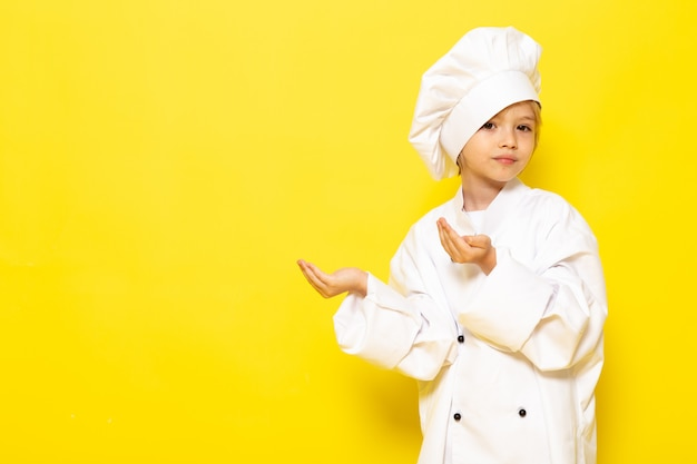 Ein niedliches kleines kind der vorderansicht im weißen kochanzug und in der weißen kochmütze, die auf dem gelben wandkind kocht, kocht essen Kostenlose Fotos