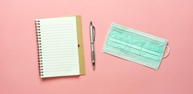 Ein notizbuch, ein stift und eine schützende gesichtsmaske Premium Fotos
